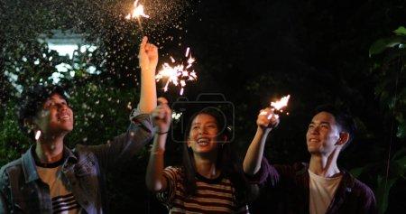 Photo pour Asiatique entre amis ayant barbecue jardin extérieur riant avec des boissons alcoolisées bière et montrant le groupe d'amis, s'amuser avec des feux de Bengale sur focus night, doux - image libre de droit