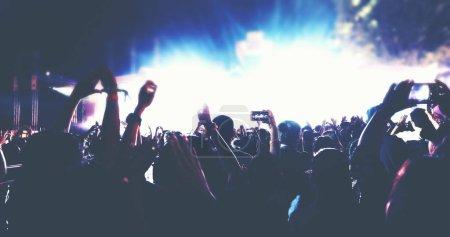 Photo pour Floue de silhouettes de foule de concert en vue de l'arrière du festival foule levant leurs mains sur les lumières de la scène lumineuse - image libre de droit