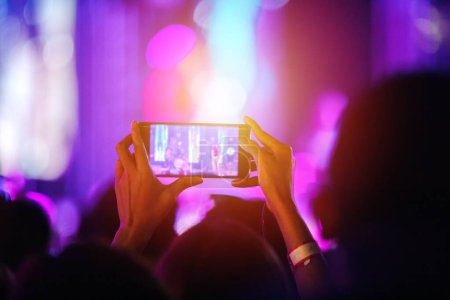 Photo for Silhouettes of concert crowd at Rear view of festival crowd raising their hands and using smartphone take photo and video on bright stage lights - Royalty Free Image