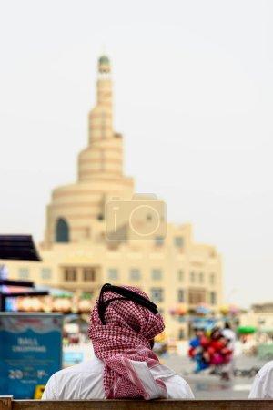 Photo pour Vue arrière de l'homme portant des vêtements arabes traditionnels et un bâtiment flou - image libre de droit