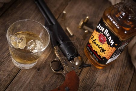 Photo for Bottle of Jim Beam honey bourbon and a glass with ice on a rustic wooden table with a western colt revolver - Country Western Background - Royalty Free Image