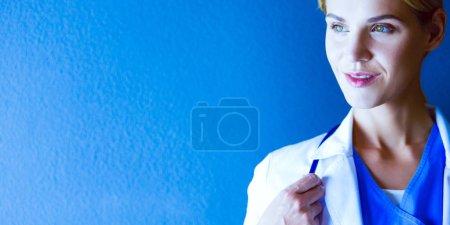 Photo pour Portrait de jeune femme médecin avec manteau blanc debout à l'hôpital - image libre de droit