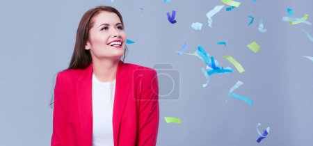 Beautiful happy woman at celebration party with confetti .Birthday or New Year eve celebrating concept.