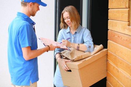 Photo pour Livreur souriant en uniforme bleu livrant la boîte de colis au destinataire concept de service de messagerie. Livreur souriant en uniforme bleu. - image libre de droit