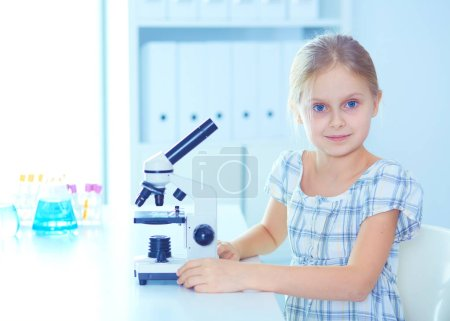 Photo pour Écolière regardant à travers le microscope en classe de sciences - image libre de droit