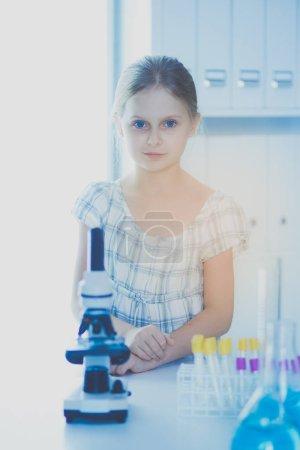Schoolgirl looking through microscope in science class.