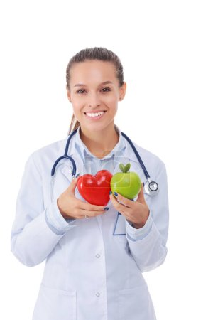 Beautiful smiling female doctor holding red heart and green apple. Woman doctor