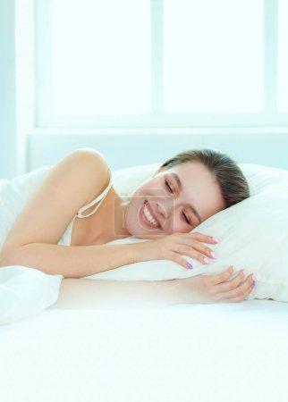 Belle fille dort dans la chambre, allongé sur le lit