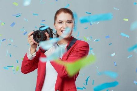 Foto de Hermosa mujer feliz con la cámara en la fiesta de celebración con confeti. Víspera de cumpleaños o año nuevo celebrando el concepto. - Imagen libre de derechos