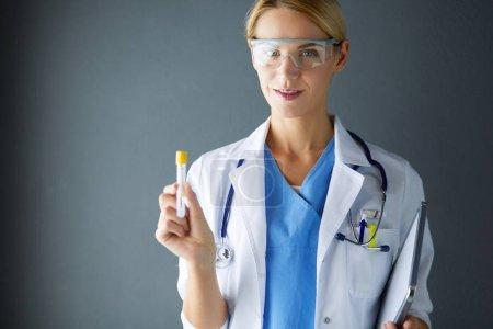 Photo pour Médecine, chercheuse scientifique ou médecin utilisant une éprouvette de solution claire dans un laboratoire ou un laboratoire - image libre de droit