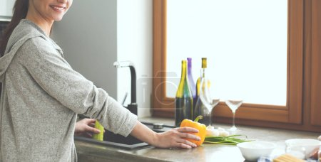 Photo for Beautiful young woman washing vegetables for salad while standing in the kitchen. - Royalty Free Image