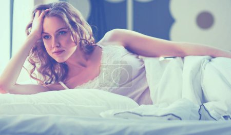 Photo for Pretty woman lying down on her bed at home. - Royalty Free Image