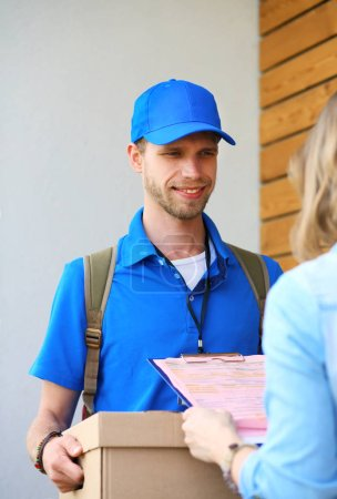 Photo for Smiling delivery man in blue uniform delivering parcel box to recipient - courier service concept. Smiling delivery man in blue uniform. - Royalty Free Image