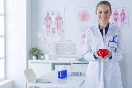 Photo pour Un médecin avec stéthoscope examinant le cœur rouge, isolé sur fond blanc. - image libre de droit