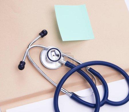 Afile folder, a stethoscope and a pen on ekg