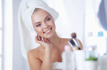 Young woman in bathrobe looking in bathroom mirror