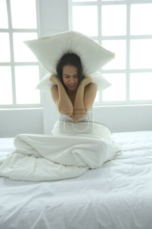 Young caucasian woman covering her head and ears with pillows.