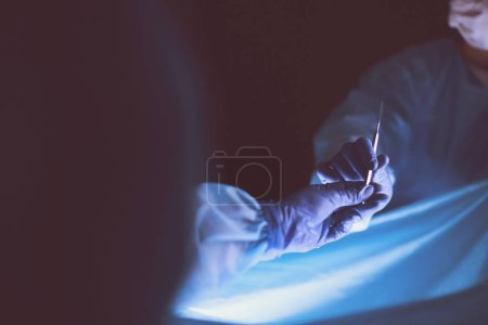 Photo for Cropped picture of scalpel taken doctors performing surgery - Royalty Free Image