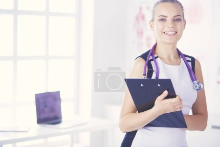 Portrait of friendly female doctor with stethoscope and tablet in hands.
