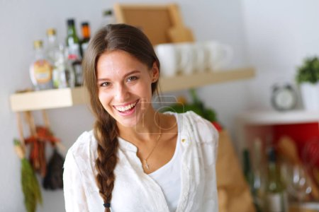Young woman standing near desk in the kitchen. Young woman .