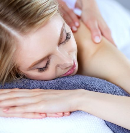 Photo pour Jeune femme allongée sur une table de massage, relaxante les yeux fermés. Femme. Salon de spa. - image libre de droit