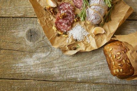 Photo pour Salami italien avec sel de mer, romarin, ail et noix sur papier. Style rustique. Gros plan. - image libre de droit