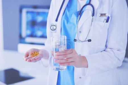 Foto de Inyección de manos de médicos sosteniendo píldoras y vaso de agua en la clínica - Imagen libre de derechos