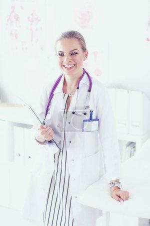 Photo pour Sourire femme médecin avec un dossier en règle uniforme. - image libre de droit