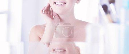 Photo pour Jeune femme en peignoir regardant dans le miroir de salle de bains. - image libre de droit