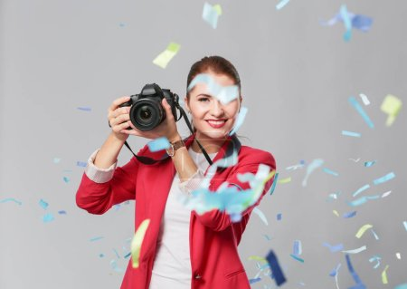 Photo for Beautiful happy woman with camera at celebration party with confetti . Birthday or New Year eve celebrating concept. - Royalty Free Image