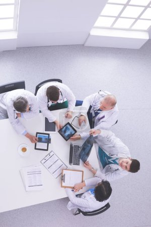 Photo for Medical team sitting and discussing at table, top view. - Royalty Free Image