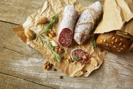 Photo pour Salami italien avec sel de mer, romarin, ail et noix sur papier. Style rustique. Vue du dessus. - image libre de droit