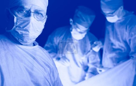 Photo for Group of surgeons at work in operating theater toned in blue. Medical team performing operation. - Royalty Free Image