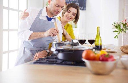 Photo pour Couples attirants dans la cuisine d'amour et ouvre le vin dans la cuisine tandis qu'ils cuisinent le dîner pour une soirée romantique. - image libre de droit