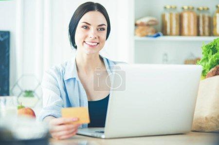 Photo pour Femme souriante, shopping en ligne à l'aide d'ordinateur et la carte de crédit dans la cuisine. - image libre de droit