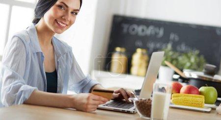 Photo pour Femme souriante, magasinage en ligne à l'aide de tablette et carte de crédit dans la cuisine. - image libre de droit