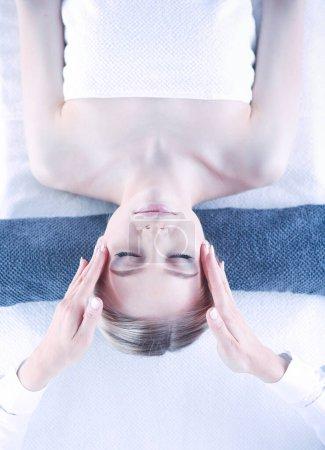 Photo pour Jeune femme allongée sur une table de massage, relaxation avec les yeux fermés. Femme. Salon spa. - image libre de droit
