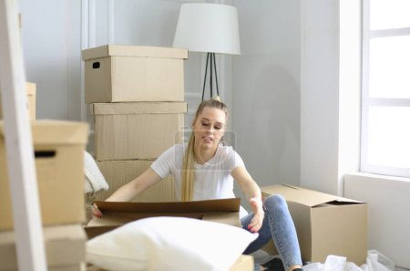 Photo for A beautiful single young woman unpacking boxes and moving into a new home. - Royalty Free Image