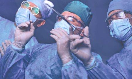 Photo pour Groupe de chirurgiens au travail en salle d'opération tonique en bleu. Équipe médicale effectuant l'opération. - image libre de droit