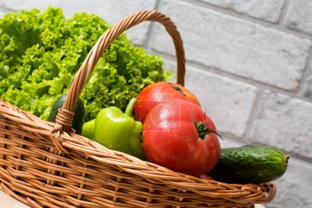 Photo for Fresh vegetables covered with water drops in basket. Organic Tomatoes, cucumber, pepper and vibrant green lettuce from the market. Fresh raw food. - Royalty Free Image