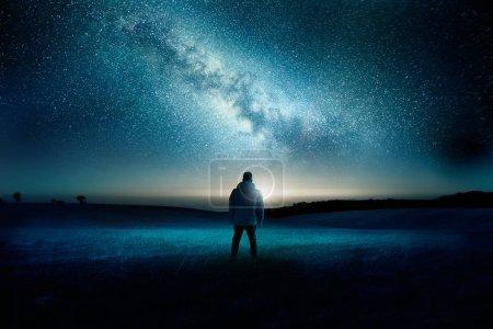 Photo pour Un homme se tient à regarder avec émerveillement et étonnement comme la lune et la voie lactée remplissent le ciel de nuit. Paysage de nuit de temps. Composite photo. - image libre de droit