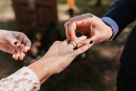 Photo pour Le marié met sur la bague de la mariée à la cérémonie de mariage - image libre de droit