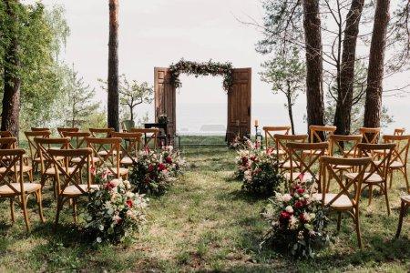 Photo pour Belle arche de mariage et chaises en bois dans le jardin, concept de cérémonie de mariage - image libre de droit