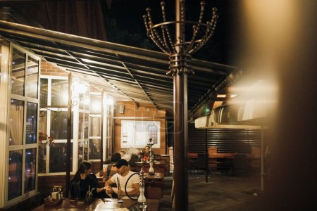 Photo for Exterior of street cafe, people spending time in cafe in evening - Royalty Free Image