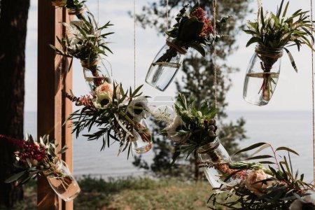 Photo pour Cadre en bois avec des bocaux en verre suspendus sur les fils. concept de décoration de mariage - image libre de droit
