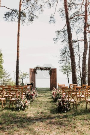 Photo for Beautiful wedding arch and wooden chairs in the garden, wedding ceremony concept - Royalty Free Image