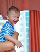 Laughing kid on  father's hands near window with red curtains and blur city modern houses outside. Happy family.