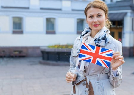 Photo pour Middle-aged woman with Great Britain flag on a background of park and city. - image libre de droit
