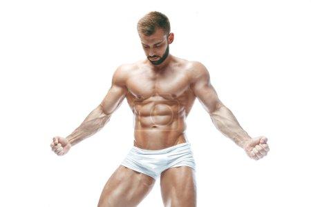 Bodybuilder posing. Beautiful sporty guy male powe...