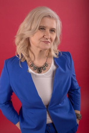 Photo for An adult beautiful woman in a blue business suit. Red background. - Royalty Free Image